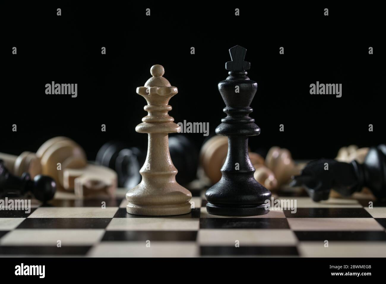 Pièces d'échecs reine et roi devant un des échiquier tombés après un champ de bataille sur un échiquier sur fond noir, concept d'abus de pouvoir Banque D'Images