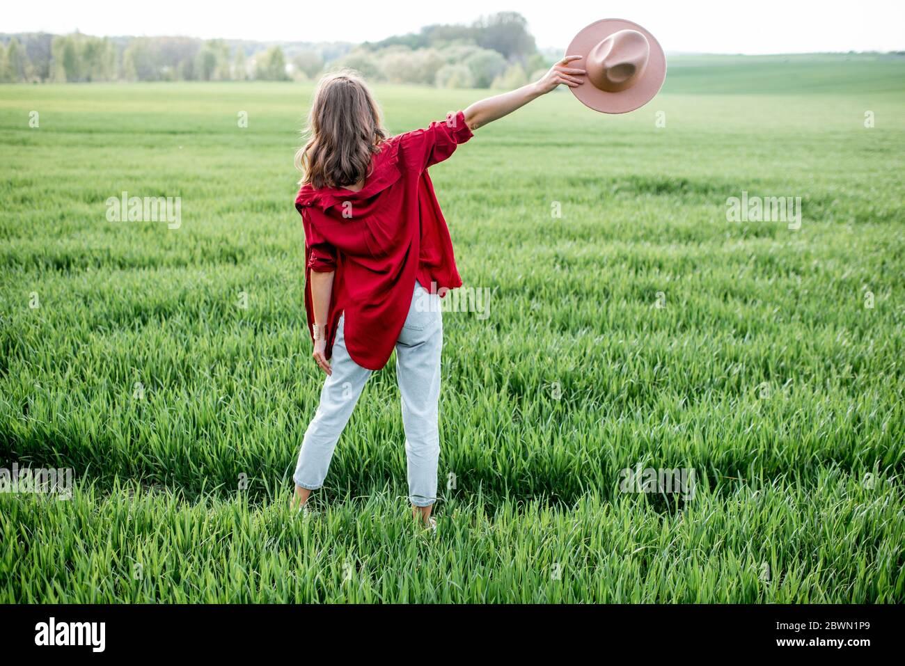 Femme élégante profitant du printemps et de la nature sur le terrain de verdure, vue arrière. Concept de vie et de liberté sans souci Banque D'Images