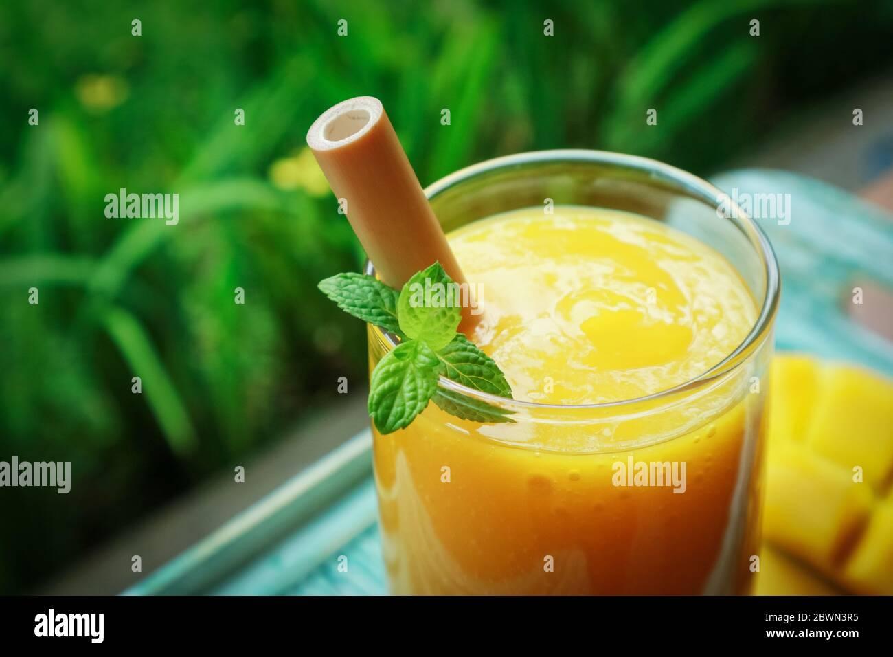 Smoothie mangue en verre avec pailles en bambou sur table en bois en extérieur, gros plan Banque D'Images