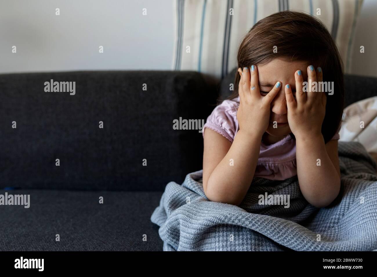 Portrait d'une fille assise sur un canapé avec un visage masqué à la maison Banque D'Images