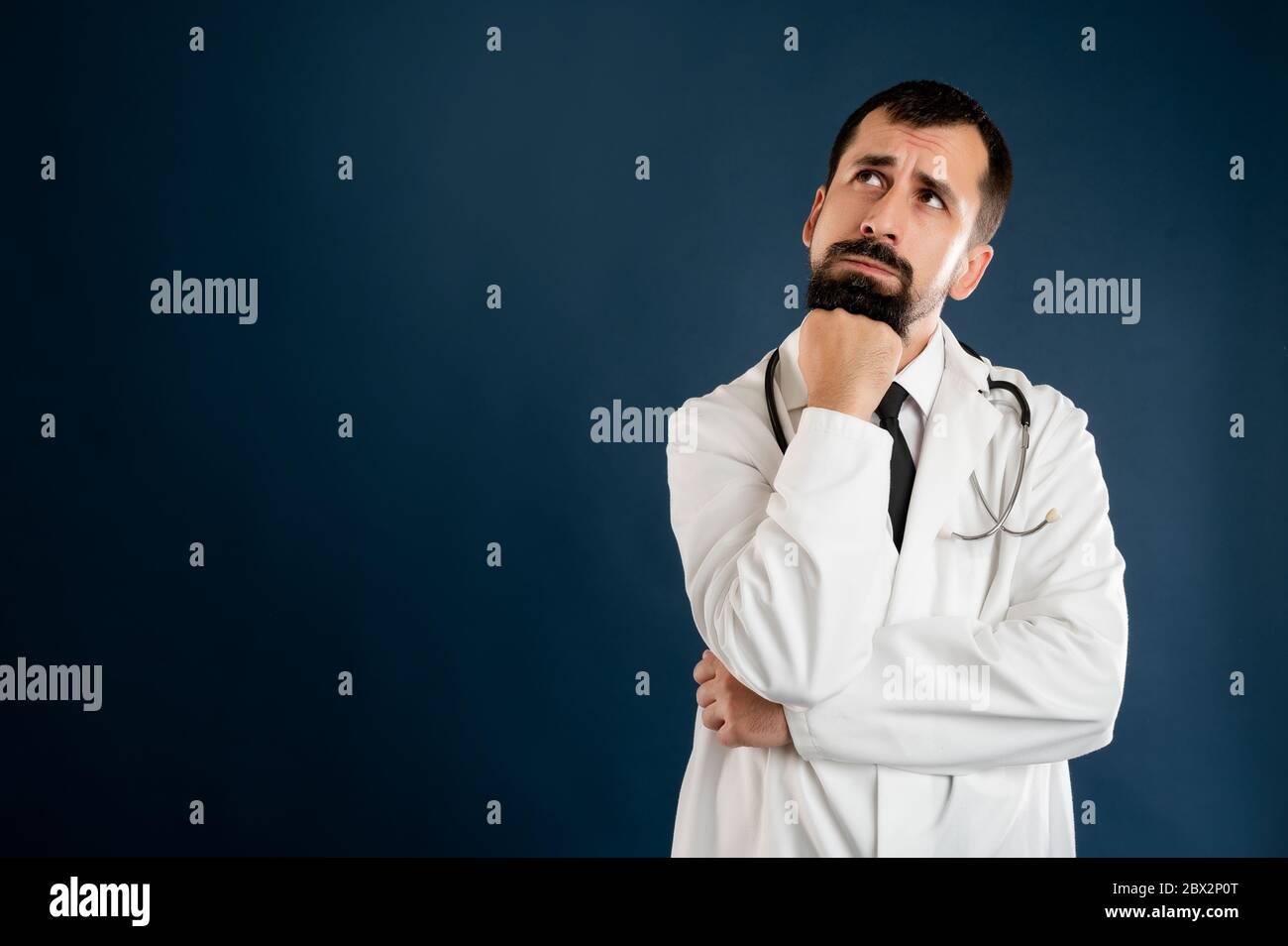 Portrait d'un médecin masculin avec stéthoscope en uniforme médical tenant la main sous son menton, ayant douteux posé sur un fond bleu isolé. Banque D'Images
