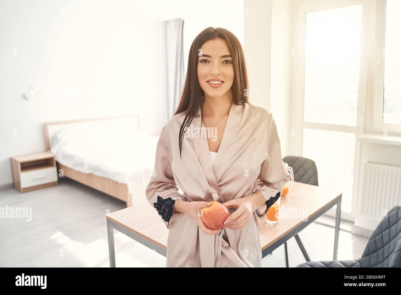 Jolie jeune femme posant à la maison avec une pomme dans les mains Banque D'Images