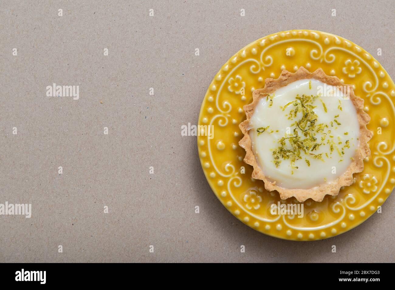 Vue de dessus de tarte au citron sur un magnifique plat jaune vintage avec une tranche de citron. Grand espace blanc pour le texte. Copier l'espace. Banque D'Images