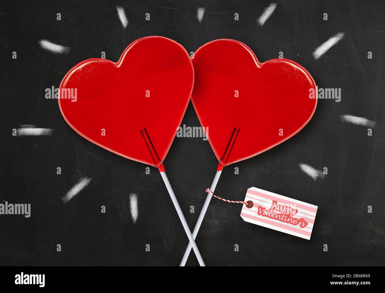 Papier mural carte de vœux de Saint-Valentin avec deux sucettes en forme de coeur rouge isolées sur un tableau noir avec des étincelles à la craie célébrant le romanti Banque D'Images