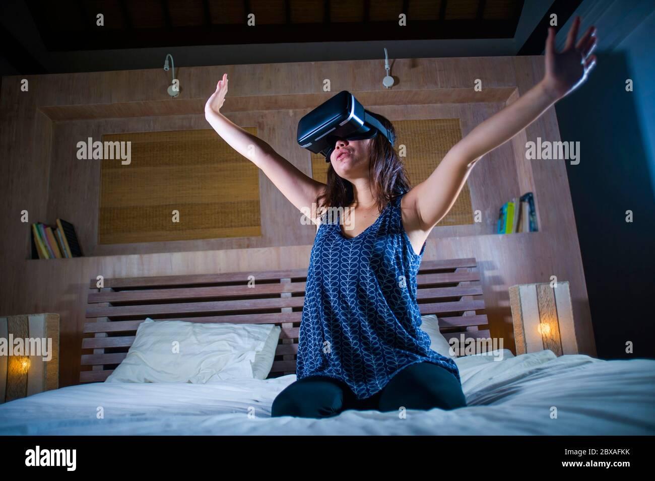 Jeune femme enthousiaste et heureuse, qui porte un casque de réalité virtuelle VR pour jouer en profitant de l'expérience 3D numérique et de regarder des touc Banque D'Images