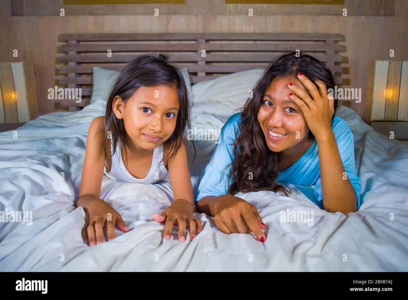 Portrait de la chambre de style de vie d'une femme asiatique heureuse à la maison posant avec sa belle fille de 8 ans dans le lit souriant ludique gai en mère et Banque D'Images