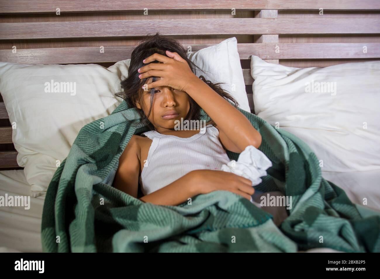 style de vie portrait à la maison de jeune belle et douce 8 ans femme enfant tenant papier de soie éternuant son nez allongé malade sur le lit ayant la grippe ou c Banque D'Images