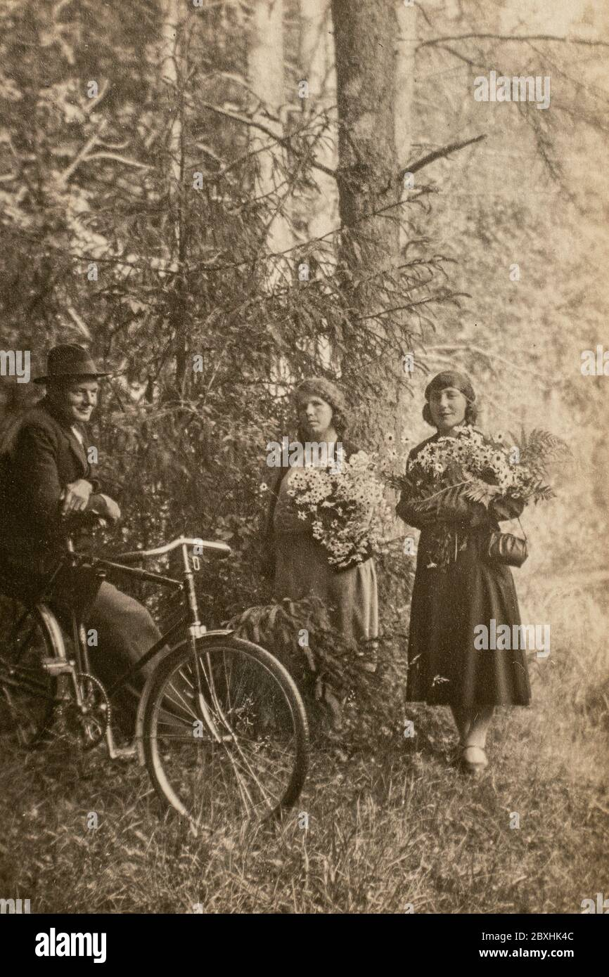 Allemagne - VERS les années 1930 : homme à vélo parlant avec deux femmes en forêt. Archive vintage art déco photo Banque D'Images