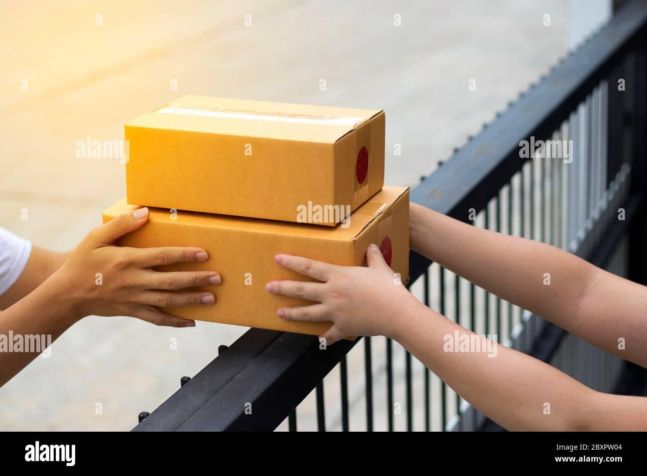 Le service de messagerie fournit la boîte marron au destinataire. La compagnie d'expédition livre les marchandises au destinataire à la porte d'entrée. Banque D'Images