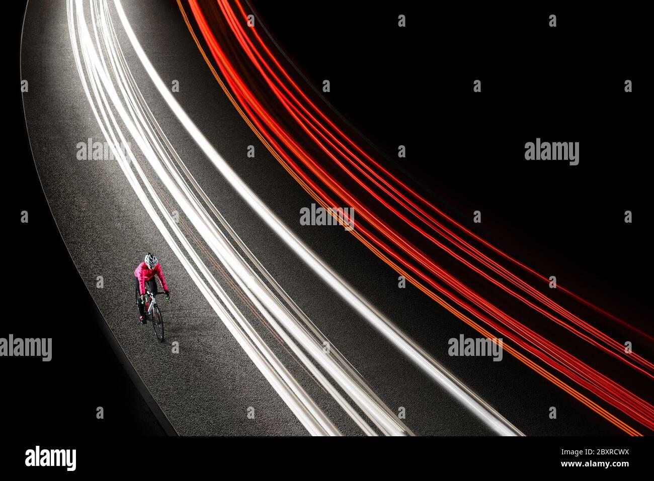 Femme cycliste en blouson rose vif à vélo sur la route de nuit avec des pistes de lumière de voitures. Concept de mode de vie sain et de sport actif urbain. Banque D'Images