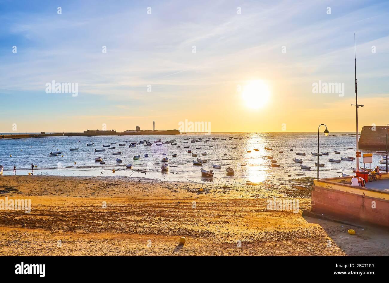 Le coucher du soleil avec de nombreux bateaux de pêche, amarrés à la plage de la Caleta avec une vue sur le château de San Sebastian à l'horizon, Cadix, Espagne Banque D'Images