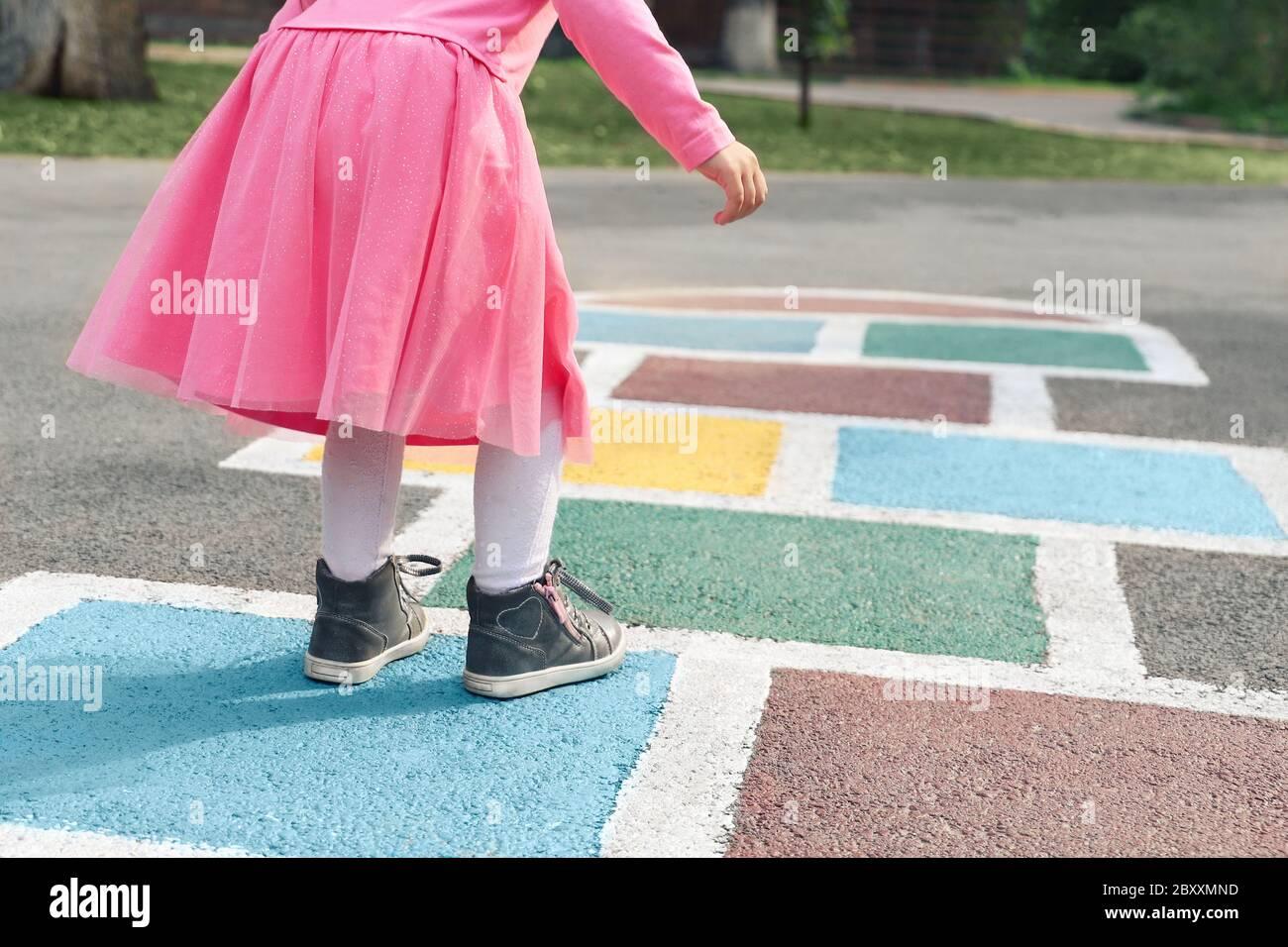Petite fille dans une robe rose jouant au hopscotch sur le terrain de jeu à l'extérieur, activités de plein air pour enfants Banque D'Images