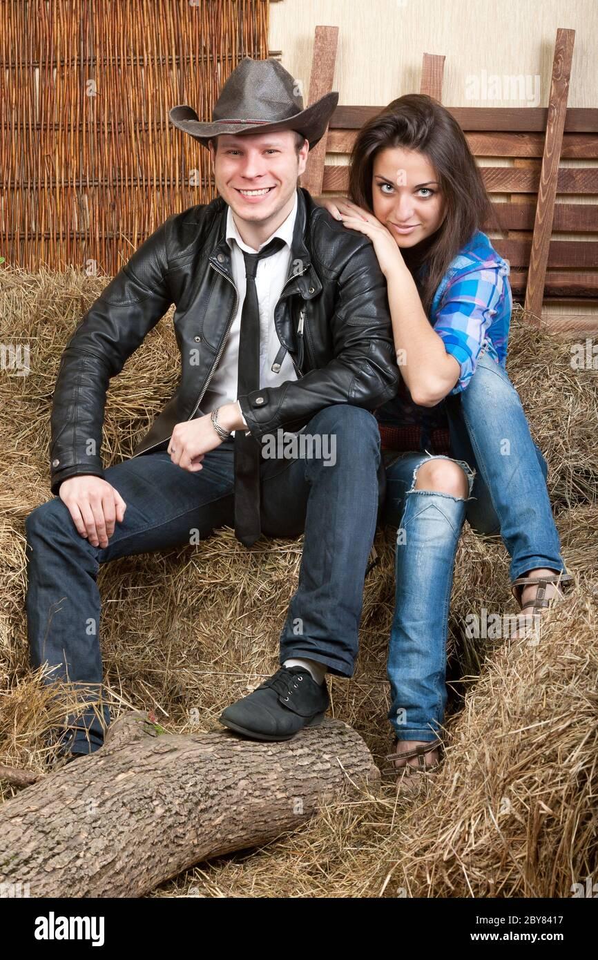 Jeunes cowboys de couple sur le foin Banque D'Images