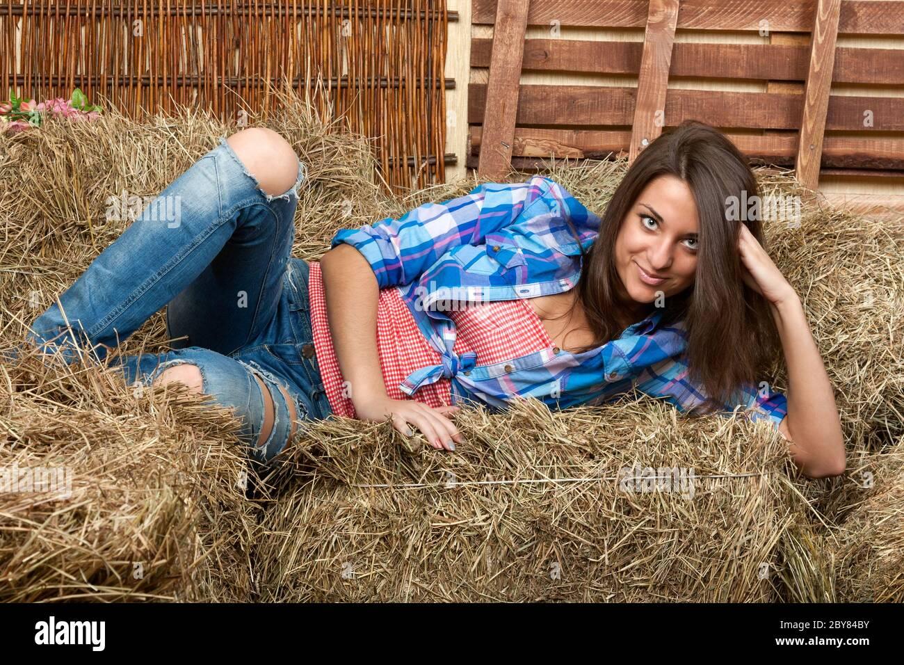 La belle fille se trouve sur une botte de foin Banque D'Images