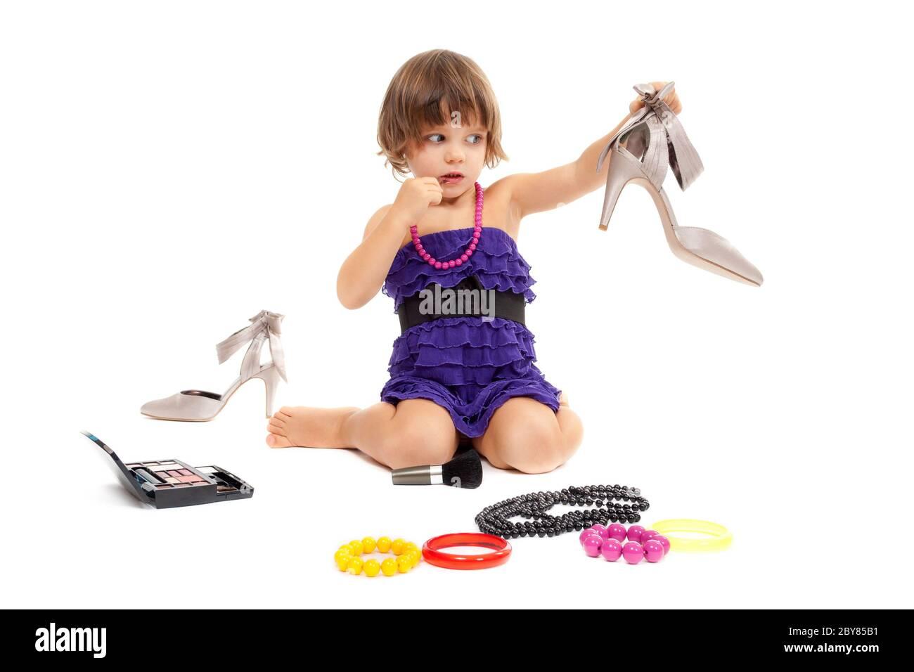 Petite fille mignonne avec des cosmétiques et des chaussures pour femmes dans le studio Banque D'Images