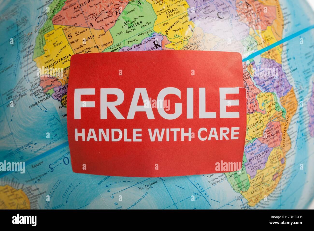 Un globe terrestre avec une main fragile et un autocollant d'entretien Banque D'Images