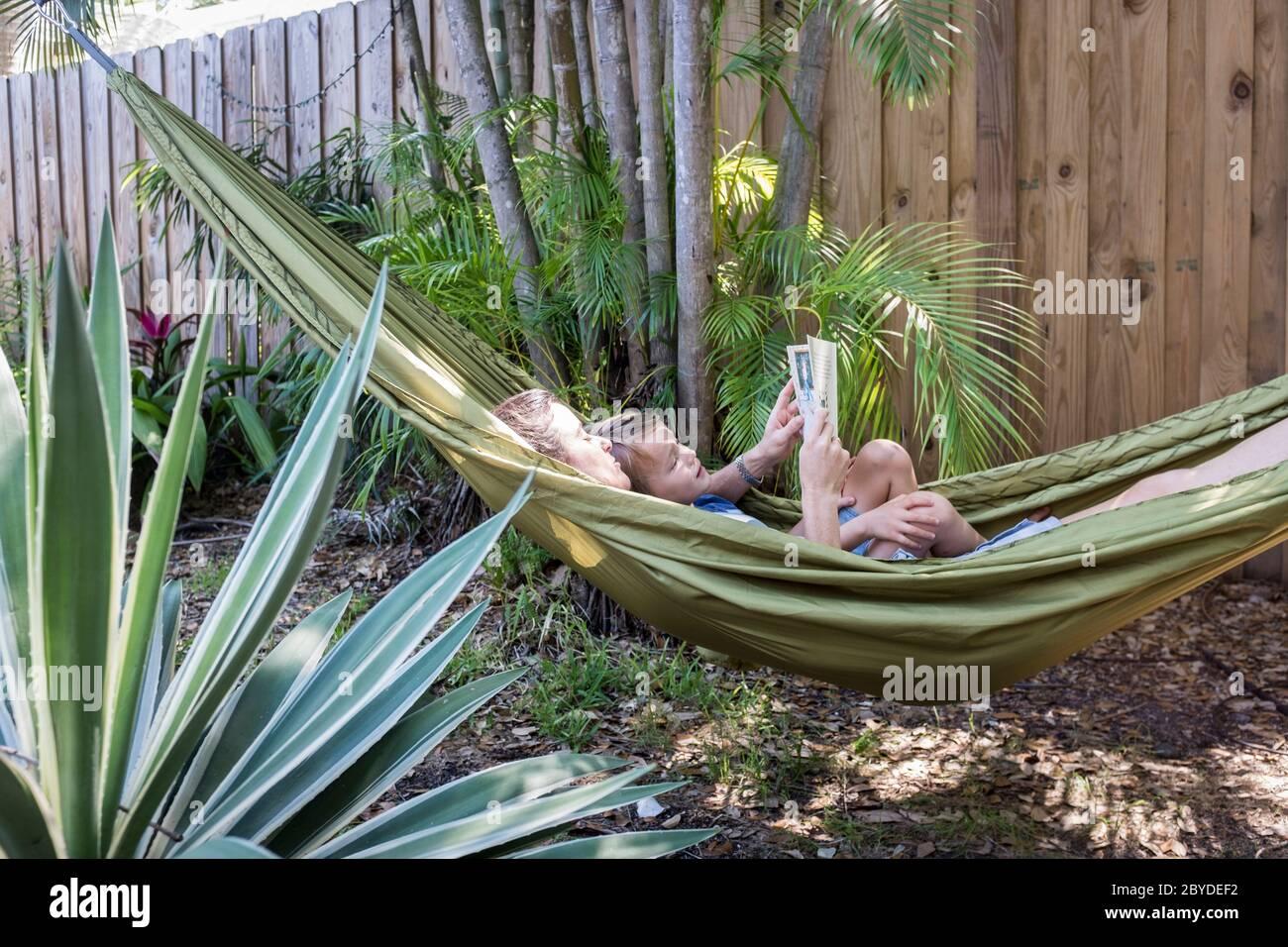 Une mère et un fils sont dans un hamac et lisent ensemble un livre d'images dans leur arrière-cour à Miami, en Floride. Banque D'Images