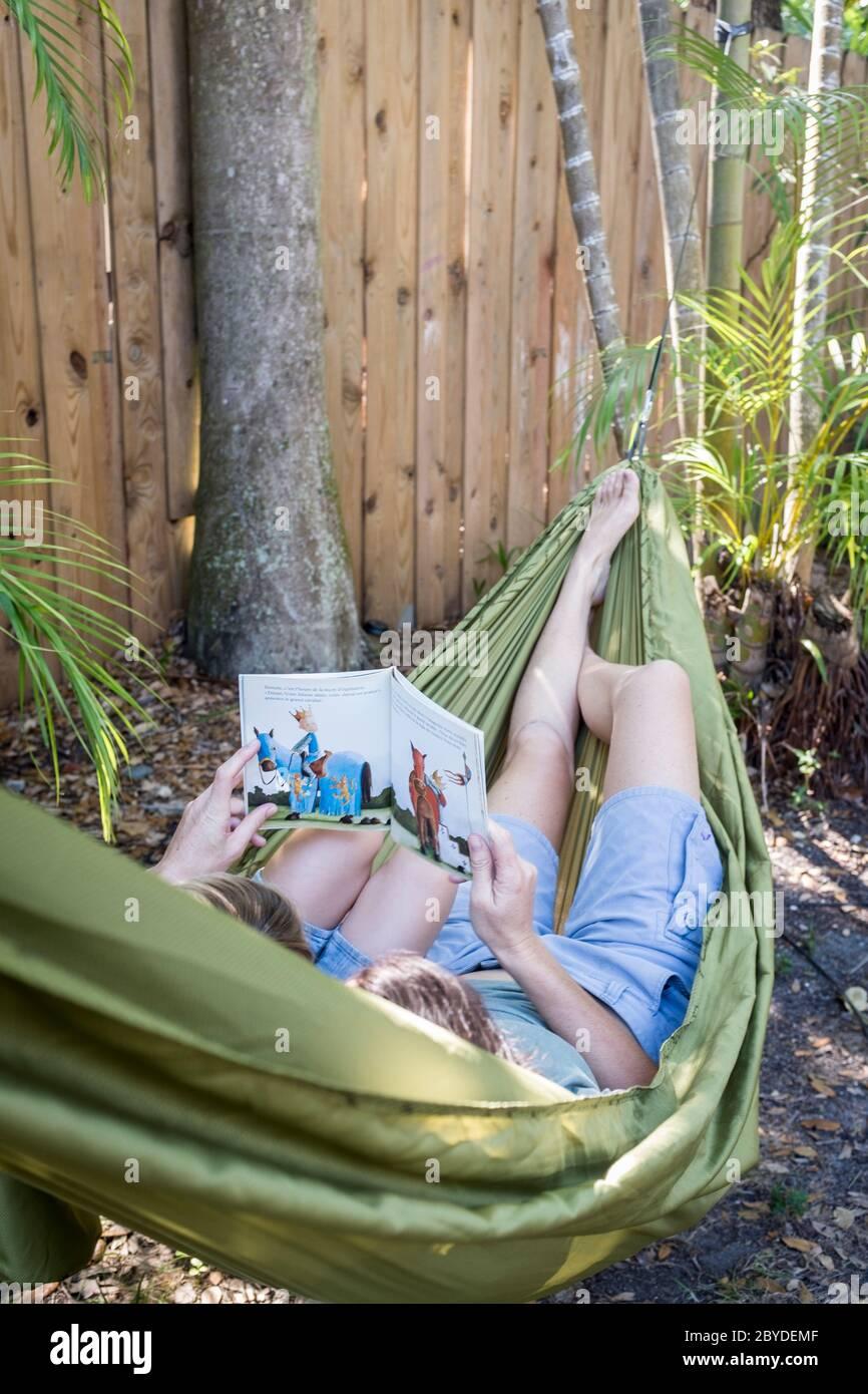 Une mère avec son petit garçon se trouve dans un hamac et lit un livre d'images ensemble dans leur arrière-cour à Miami, en Floride. Banque D'Images