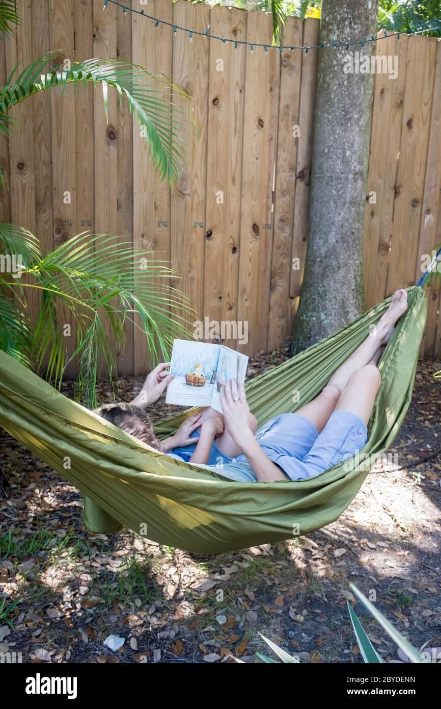 Une mère montre à son petit garçon un livre d'images comme ils se trouvent dans un hamac ensemble dans leur arrière-cour à Miami, Floride. Banque D'Images