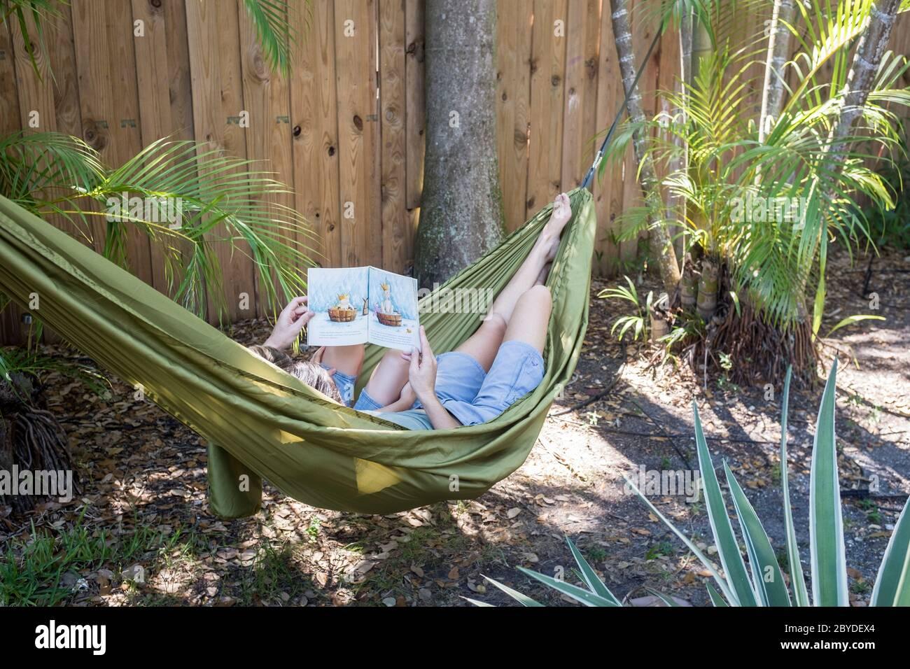 Une mère et son petit fils sont dans un hamac et lisent ensemble un livre d'images dans leur arrière-cour à Miami, en Floride. Banque D'Images