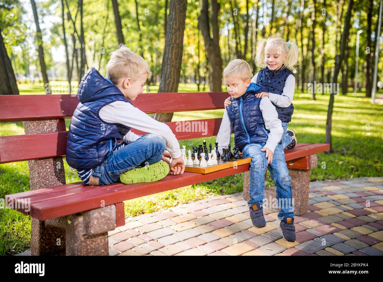 Petits écoliers jouant aux échecs dans le parc sur le banc. Vacances d'été, jeux intellectuels. Club d'échecs pour enfants. Bonne enfance et enfants Banque D'Images