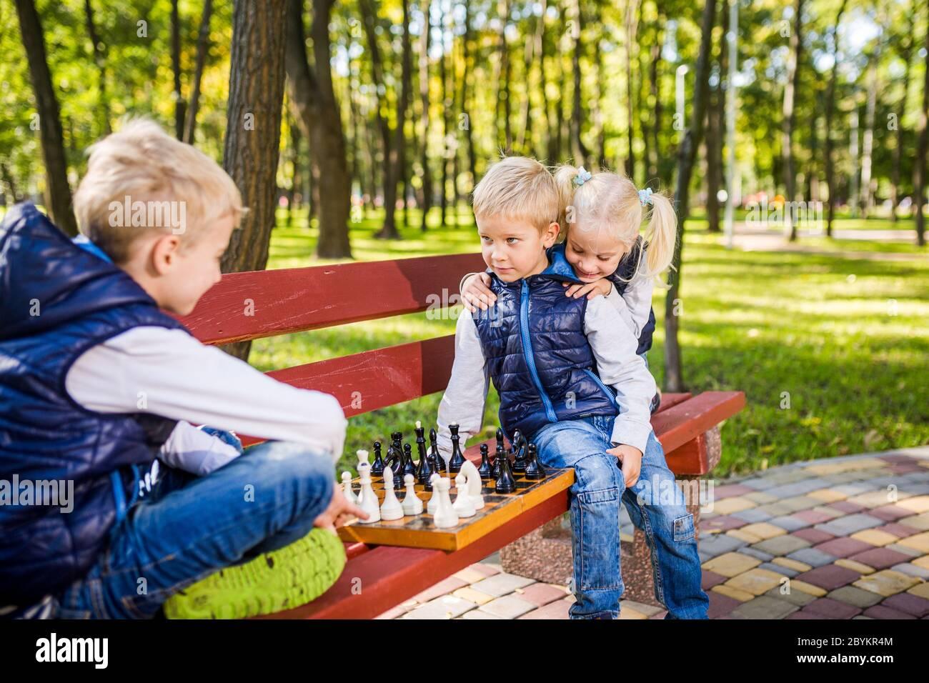 Petits frères jouant aux échecs avec sœur sur banc dans le parc. Développement de l'intelligence des enfants. Loisirs en famille. Enfants jouant aux échecs à l'échiquier Banque D'Images