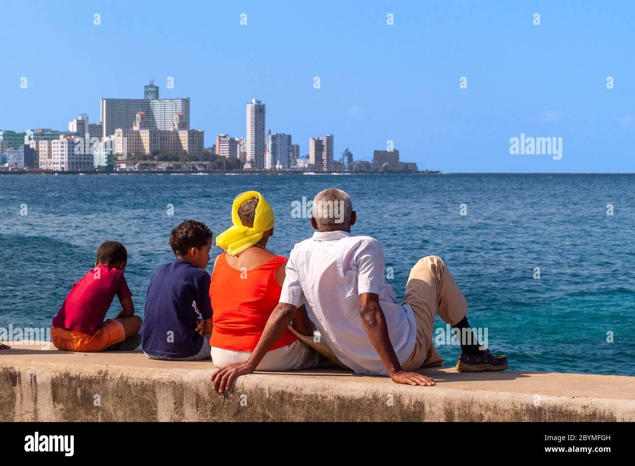 Groupe familial assis sur le mur d'El Malecon, la Havane, Cuba Banque D'Images