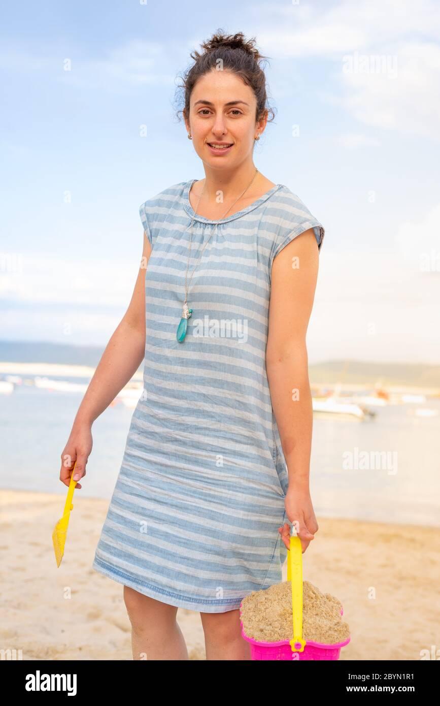 Belle jeune femme sur la plage avec la benne et spade, Espagne Banque D'Images