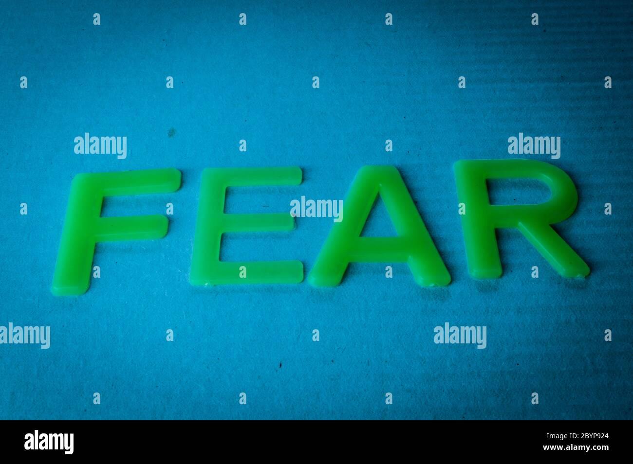 Peur. Mot composé de lettres vertes sur fond bleu. Banque D'Images