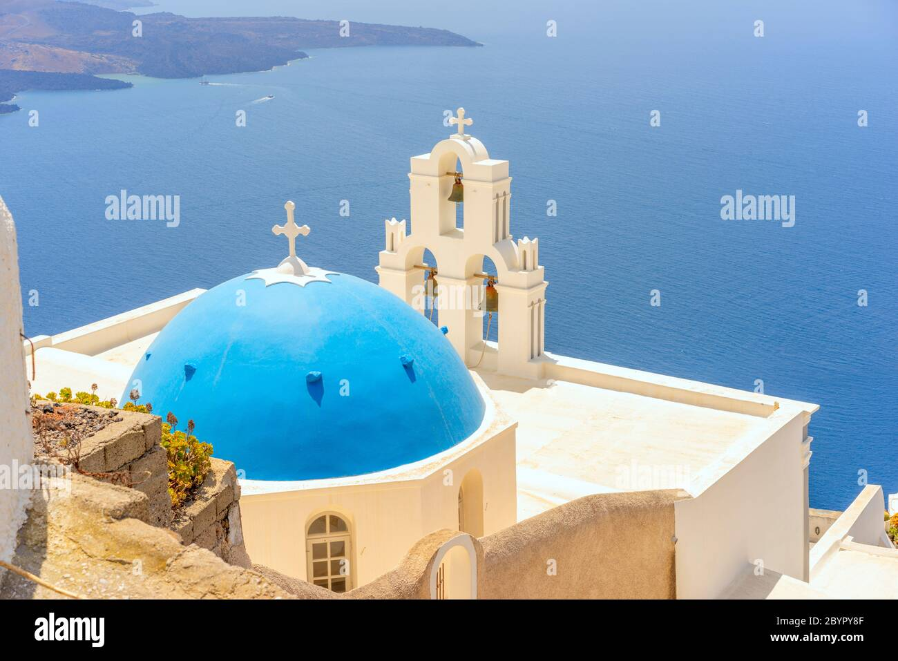 L'église catholique Marie en dôme bleu et les trois cloches de Fira sur l'île grecque de Santorin, surplombant la caldeira et la mer Égée Banque D'Images