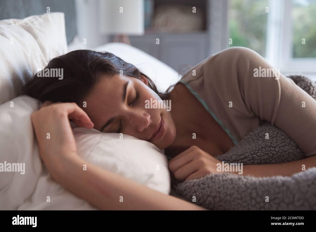 Femme de race mixte couché sur le lit pendant la pandémie du coronavirus 19 Banque D'Images