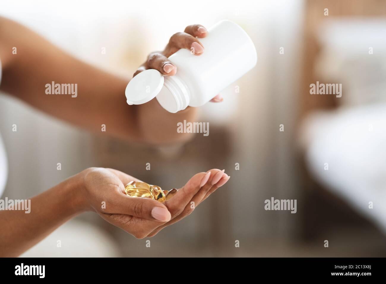 Non reconnaissable Black Female verse hors capsules de supplément de nourriture de vitamine hors de la bouteille Banque D'Images