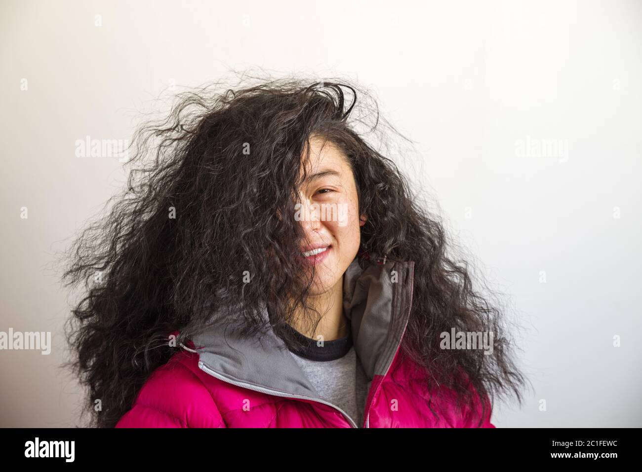 femme asiatique avec de grands cheveux ondulés et fous couvrant la moitié de son visage Banque D'Images