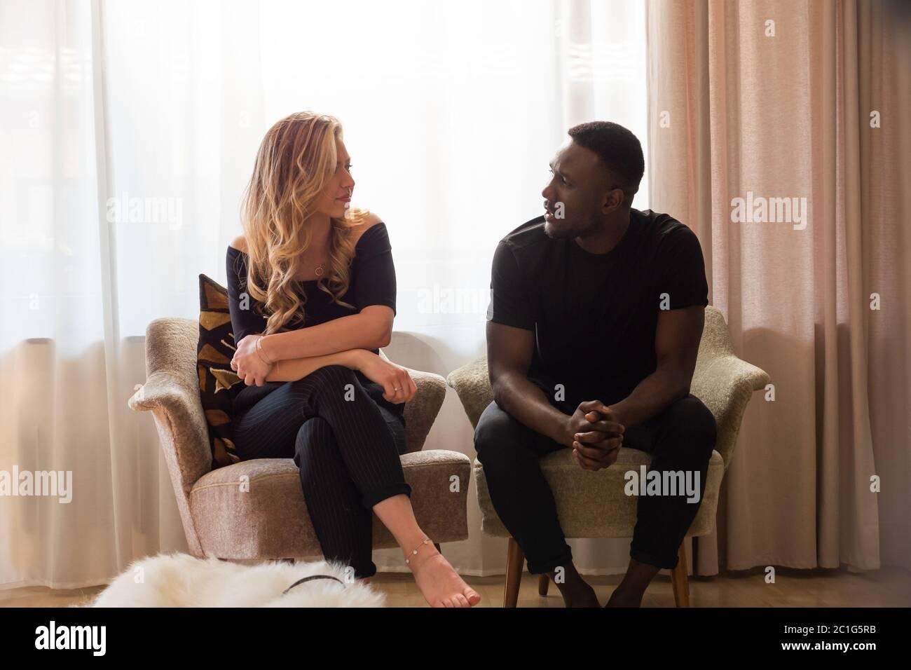 Portrait d'un couple de race mixte assis dans des fauteuils séparés parlant. Longueur totale. Banque D'Images