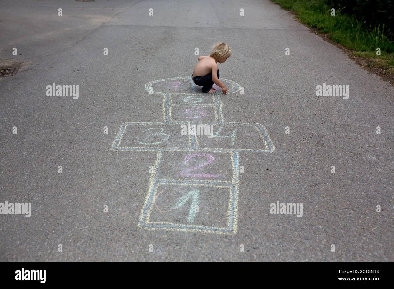 Enfant, blond, jouant au hopscotch dans la rue, l'été Banque D'Images
