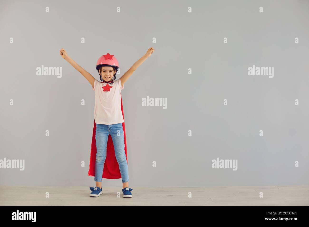 Le petit super-héros de bébé dans un casque sourit ses mains tout en se tenant sur un fond gris. Banque D'Images