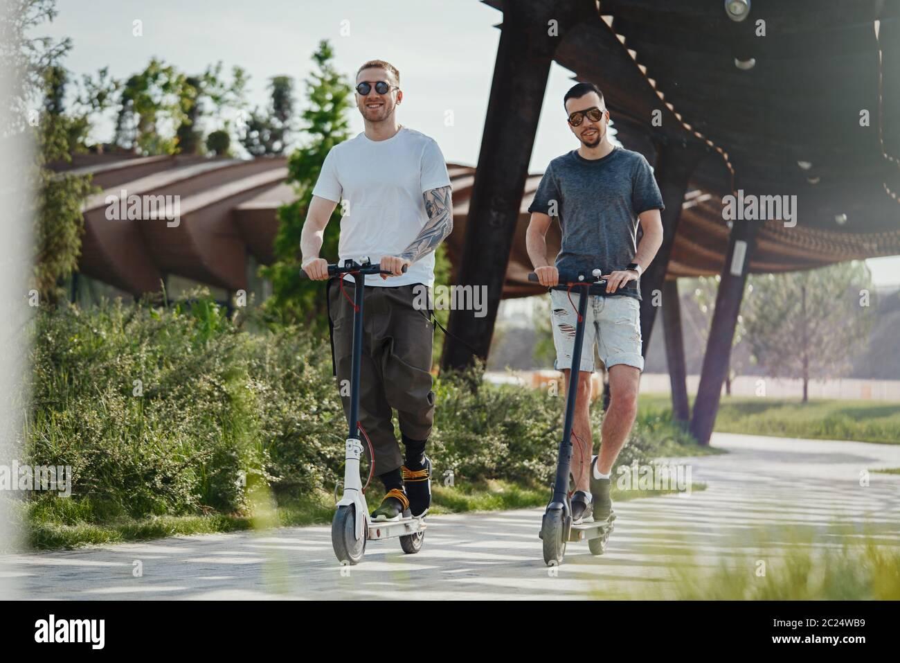 Deux beaux hommes qui font des scooters électriques dans un magnifique parc paysage Banque D'Images