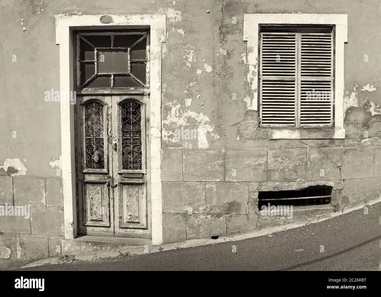 l'avant d'une ancienne maison abandonnée avec des fenêtres avec volets et porte en bois fermée avec des éclats de peinture sur une rue en pente Banque D'Images