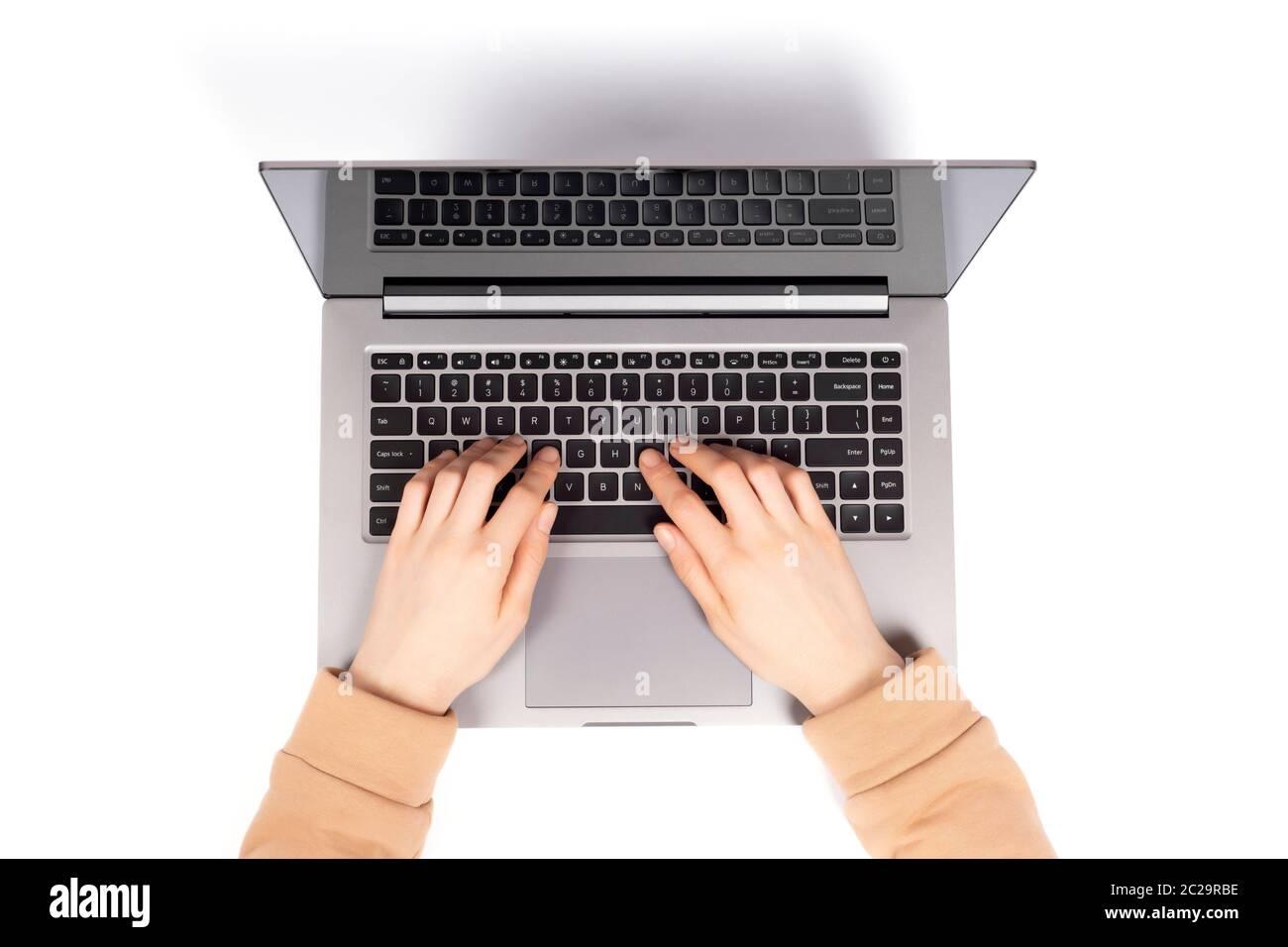 Personne travaillant sur un ordinateur portable dans un espace moderne. Mains de femmes travaillant sur un nouvel ordinateur portable isolé sur fond blanc vue du dessus, plat. Banque D'Images