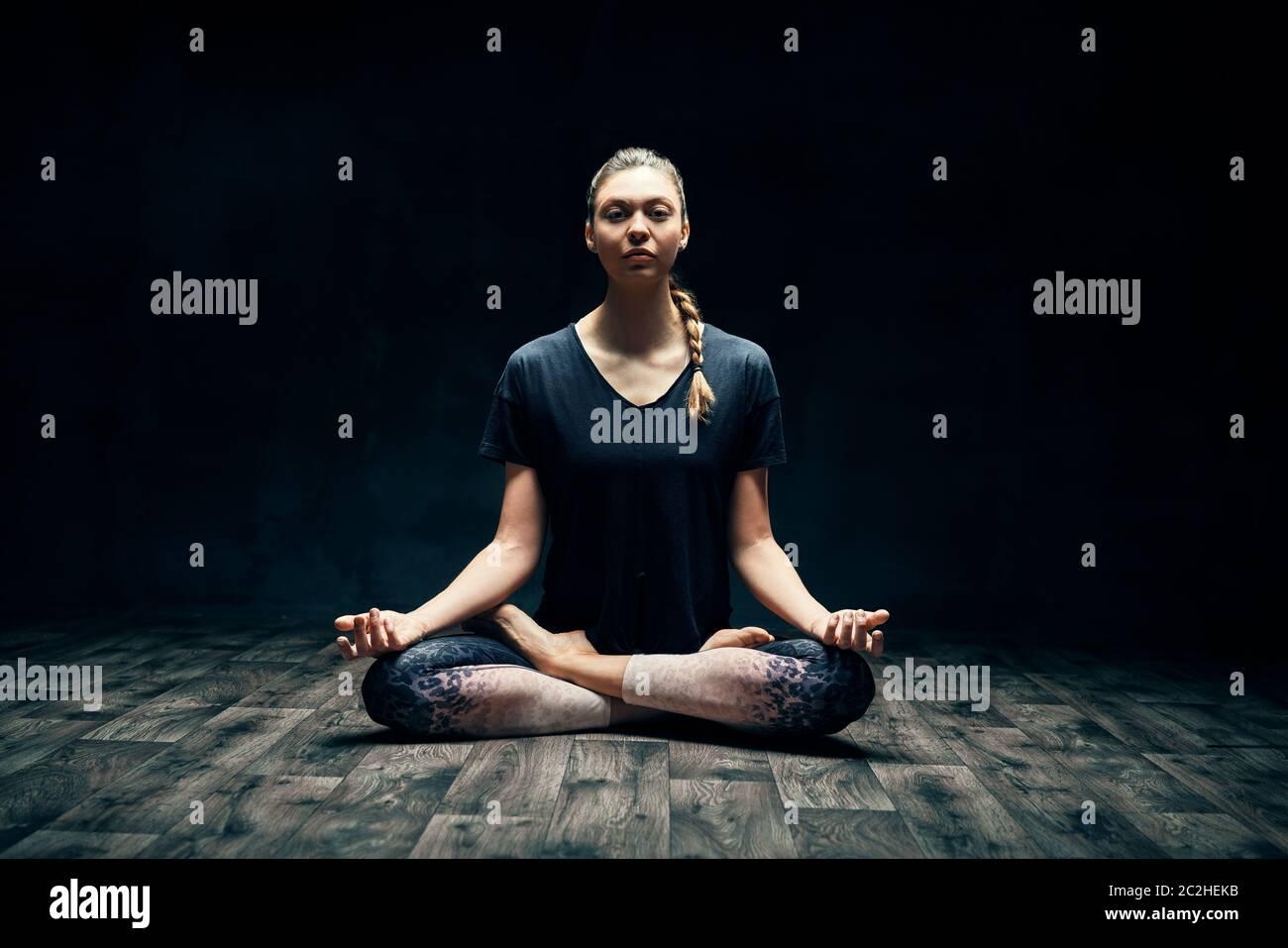 Jeune femme attrayante pratiquant le yoga assis dans la pose de lotus et méditant dans la pièce sombre Banque D'Images