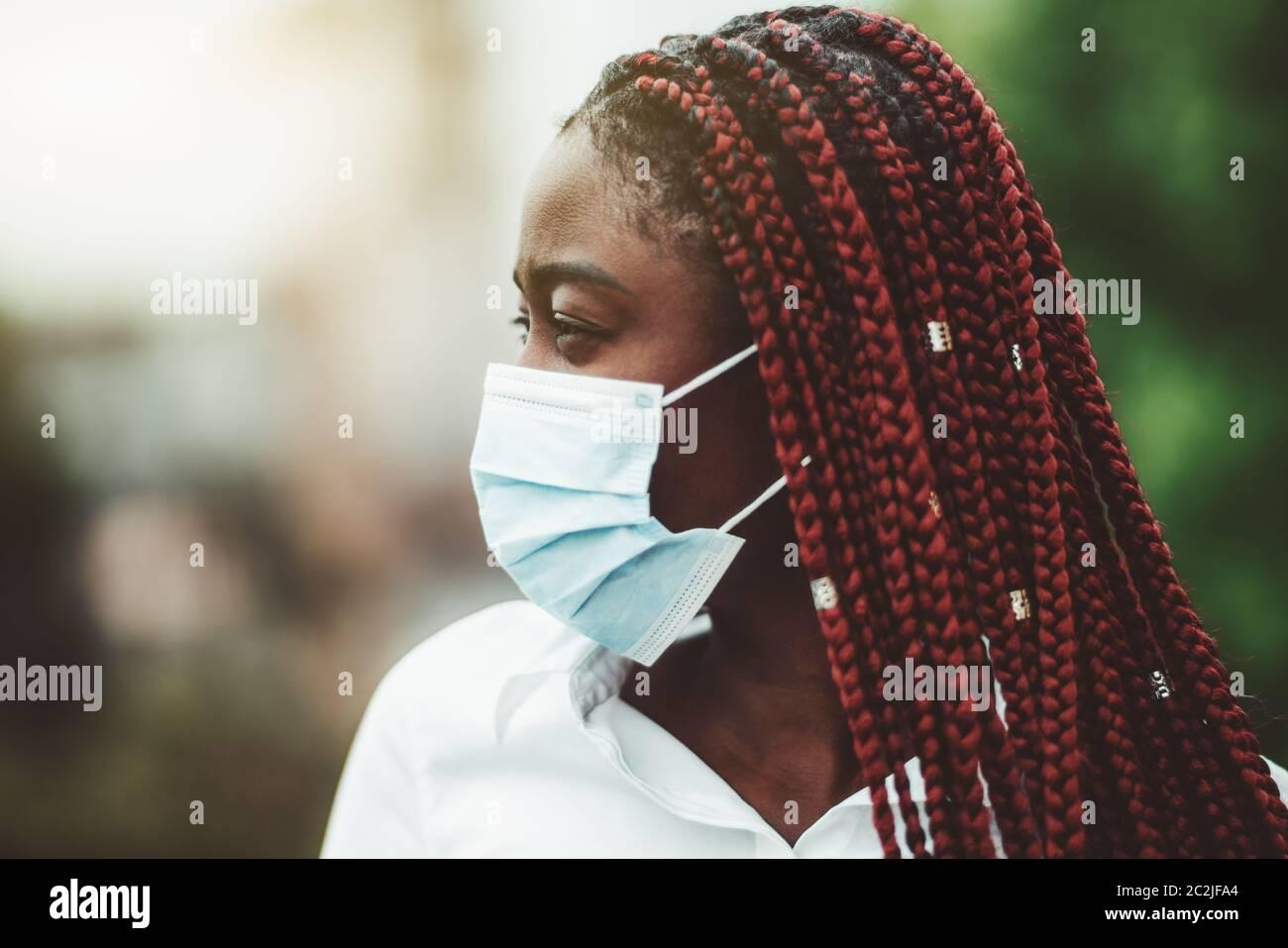 Portrait rapproché d'une jeune femme africaine avec des tresses de châtaignier et dans un masque de protection contre le virus sur son visage; femme noire masquée à l'extérieur - protection Banque D'Images