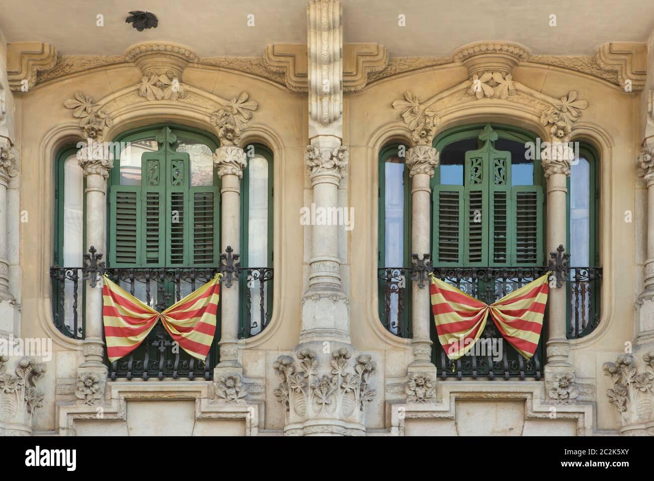Drapeaux nationaux catalans placés sur les balcons français des caisses Ramos à Barcelone, Catalogne, Espagne. Le bâtiment conçu par l'architecte moderniste catalan Jaume Torres i Grau a été construit entre 1906 et 1908 sur la Plaça de Lesseps (Plaza de Lesseps). Banque D'Images