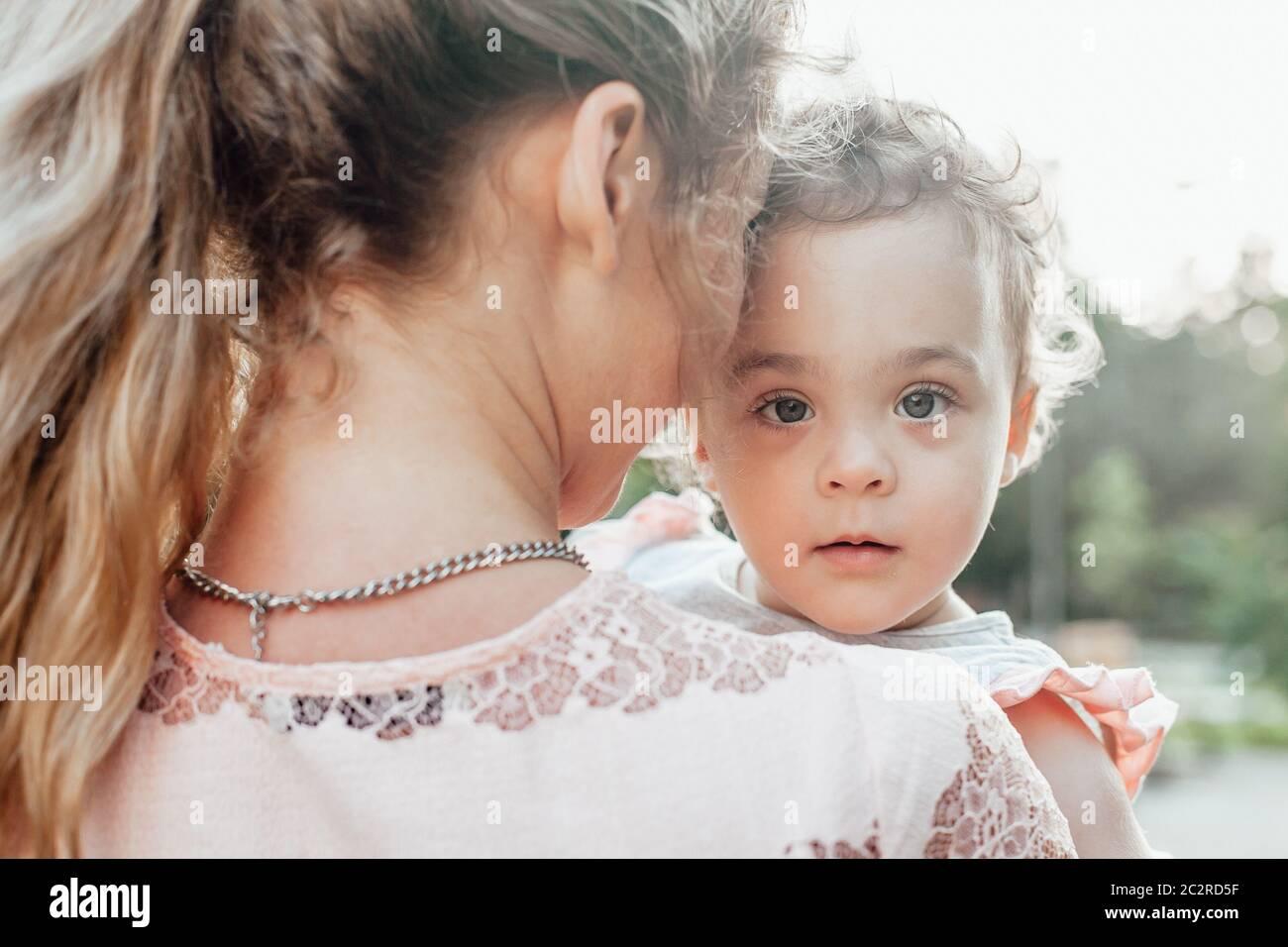 Portrait d'une jeune fille tenue par sa mère Banque D'Images