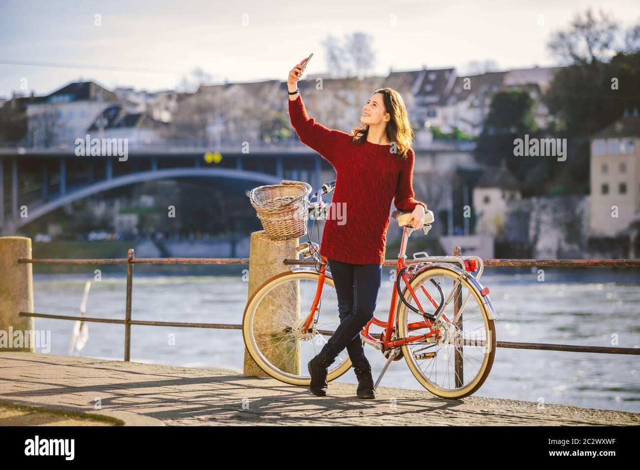 Une belle jeune femme avec un vélo rouge rétro fait une photo d'elle-même dans la vieille ville d'Europe sur l'éban du Rhin Banque D'Images