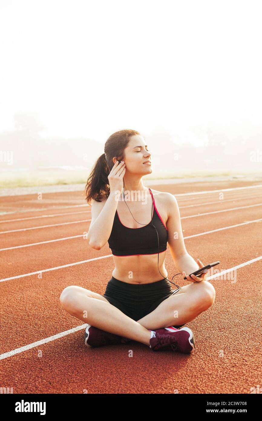 De plus, une jeune athlète joyeuse et souriante, assise sur une piste de course rouge et se reposer après un entraînement au stade par beau temps d'été Banque D'Images