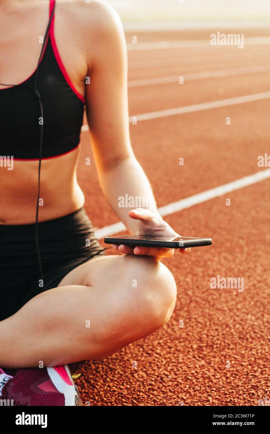 Athlète féminine détendue assise sur la piste de course après l'entraînement Banque D'Images