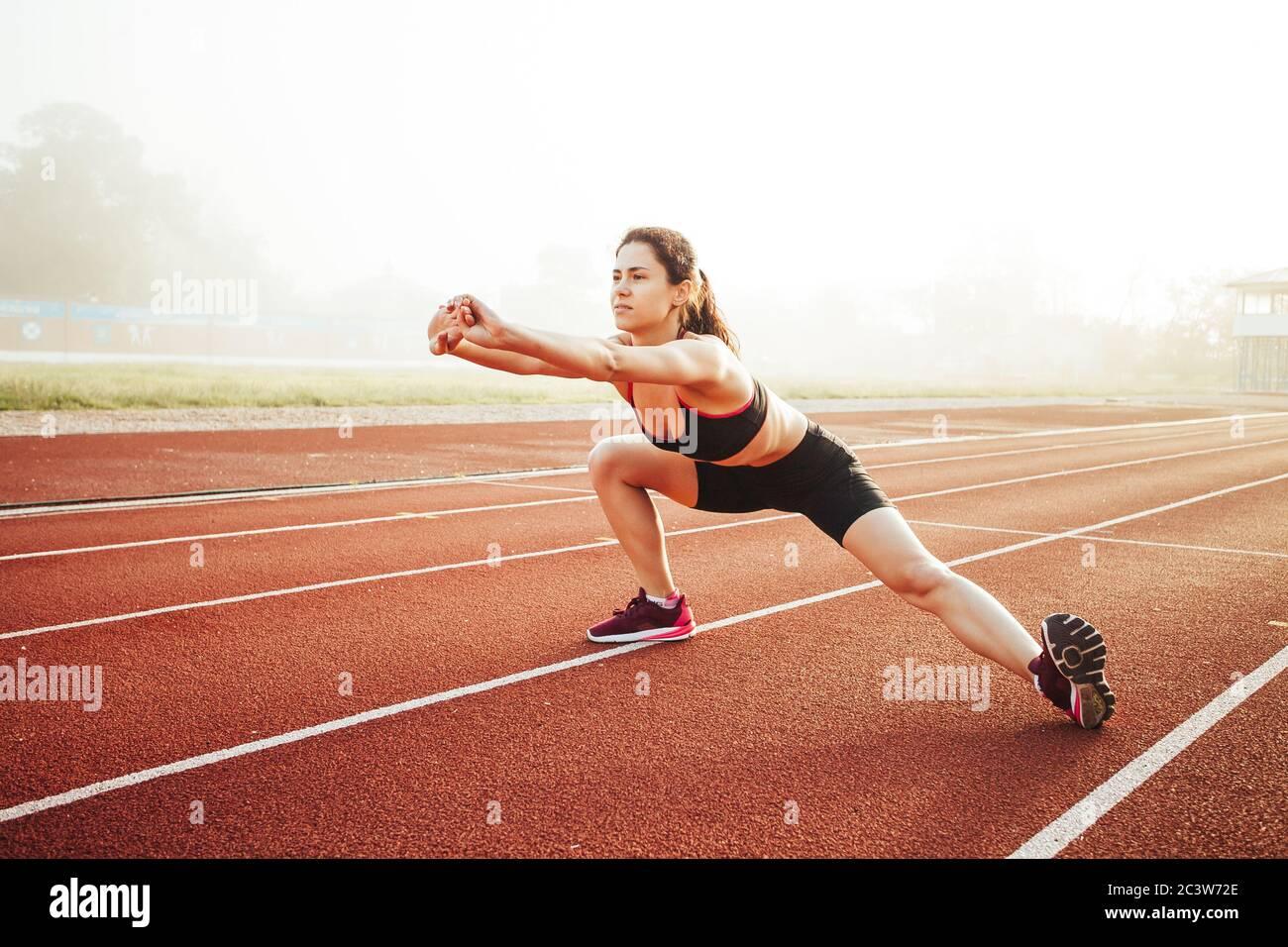 Femme athlétique qui s'étire sur la piste de course avant l'entraînement, santé physique farce Banque D'Images