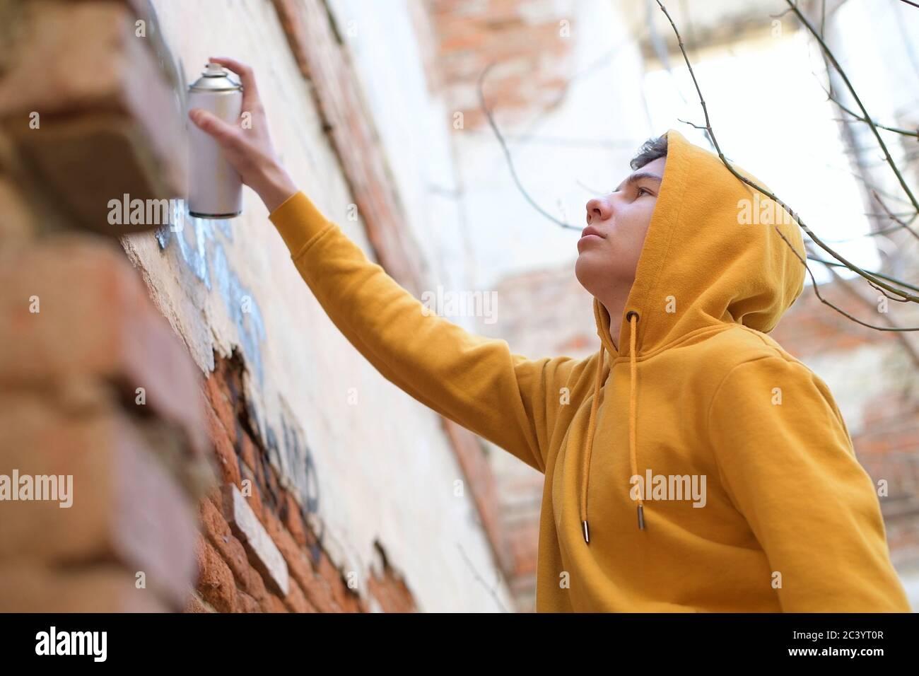 Un adolescent tient une bombe dans sa main et place des inscriptions sur le mur Banque D'Images