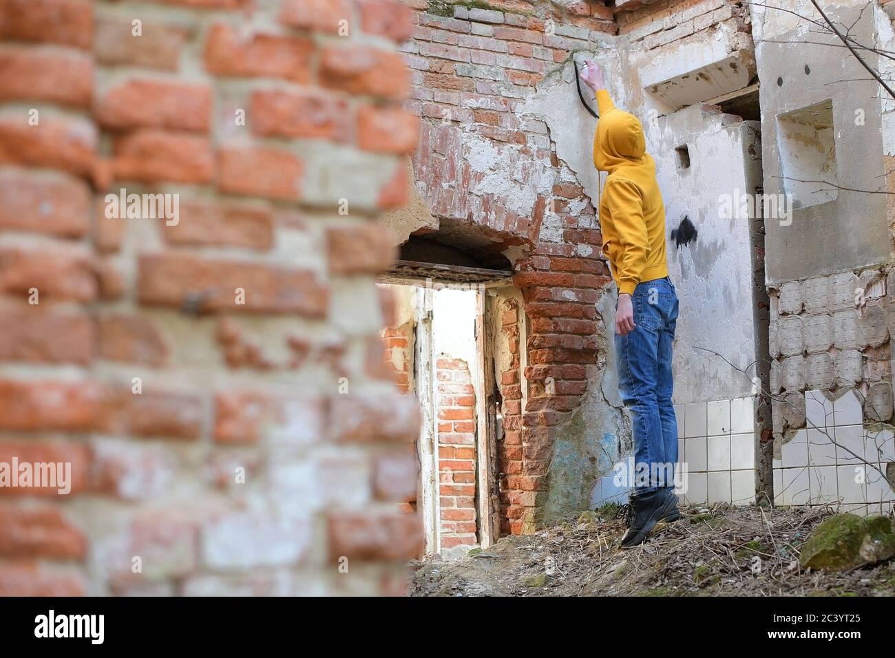Un jeune homme dessine de la peinture en aérosol sur le mur d'un bâtiment abandonné Banque D'Images