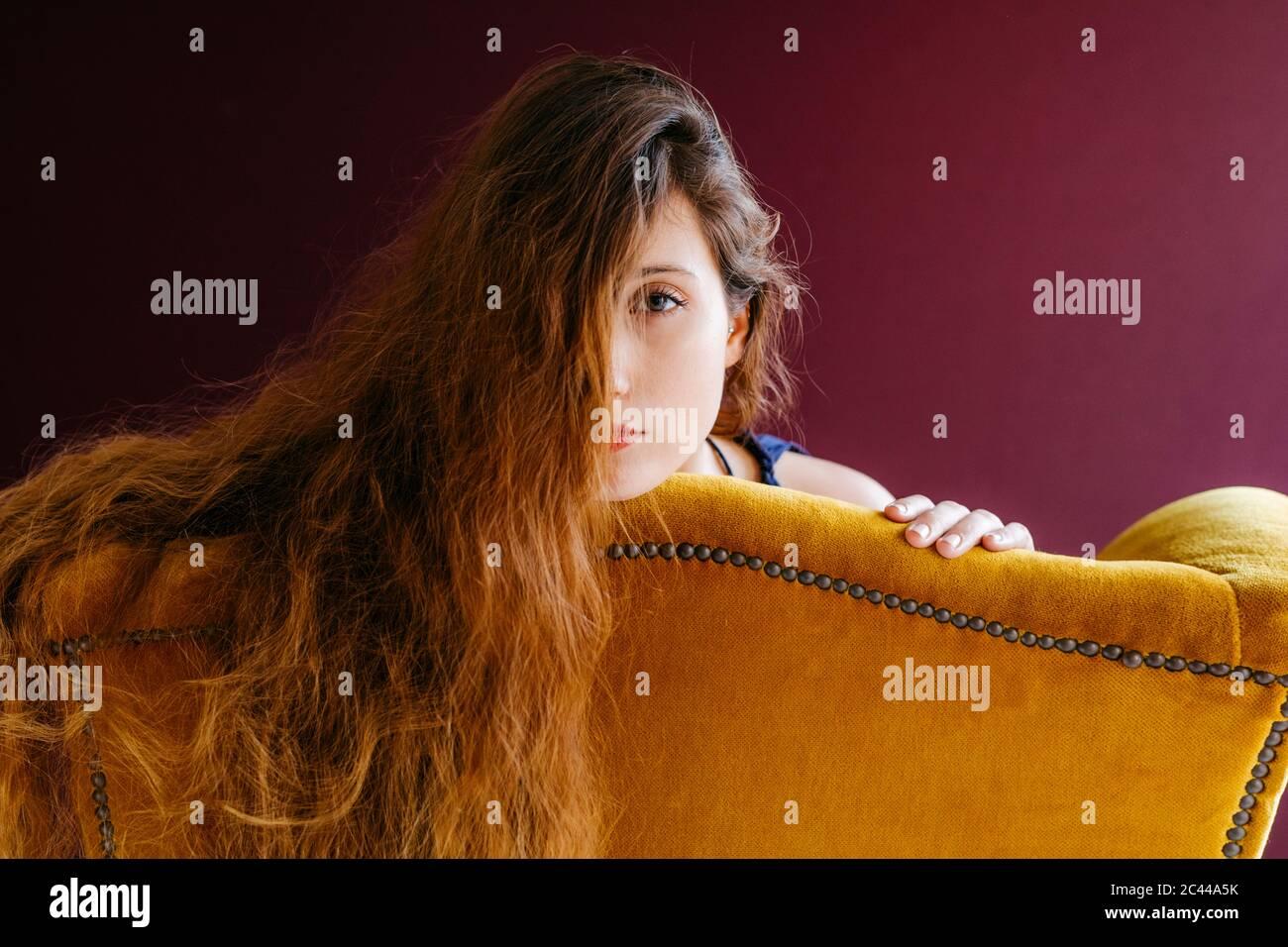 Portrait rapproché de la jeune femme avec de longs cheveux bruns, adochée sur une chaise dorée sur un fond coloré Banque D'Images